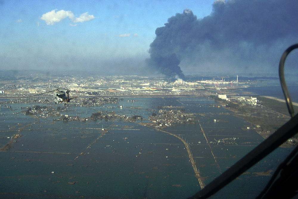 An aerial view of the Sendai region with black smoke coming from the Nippon Oil refinery. By U.S. Navy photo [Public domain], via Wikimedia Commons