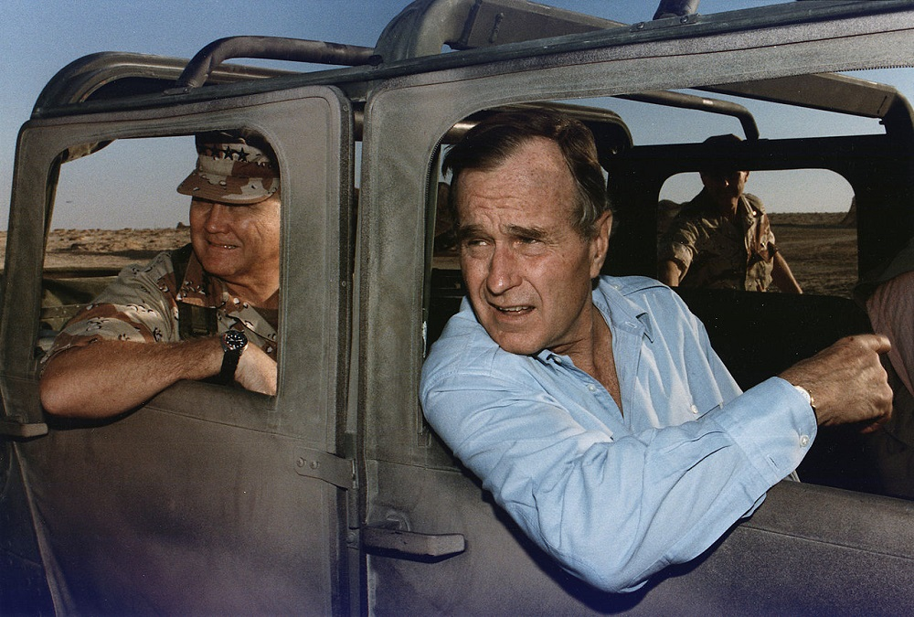 President Bush rides in a HUMVEE with General H. Norman Schwarzkopf during his visit with troops in Saudi Arabia on Thanksgiving Day 1990