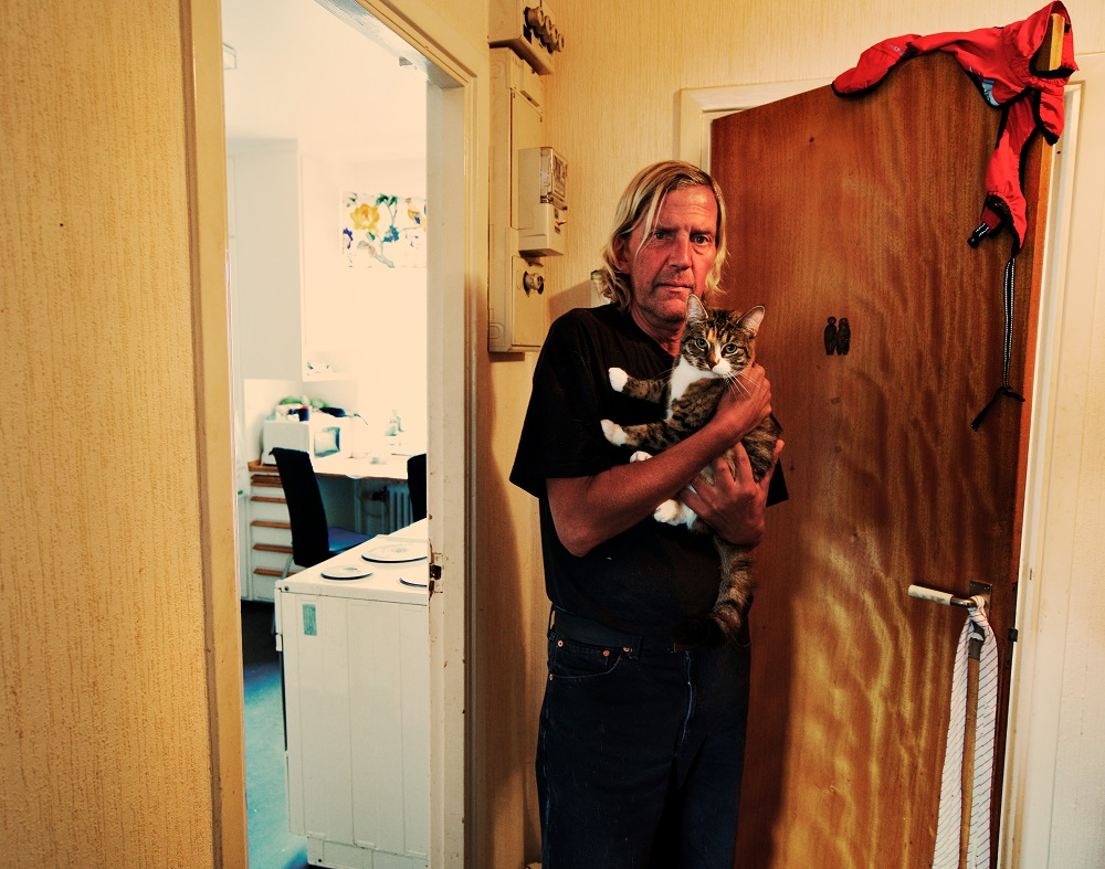 Selling Faktum has helped Bertil Schmidt (September) overcome his social anxieties and afford his own place. He stands in the apartment he now shares with a dog and three cats. Credit: Håkan Ludwigson and Bo Kågerud