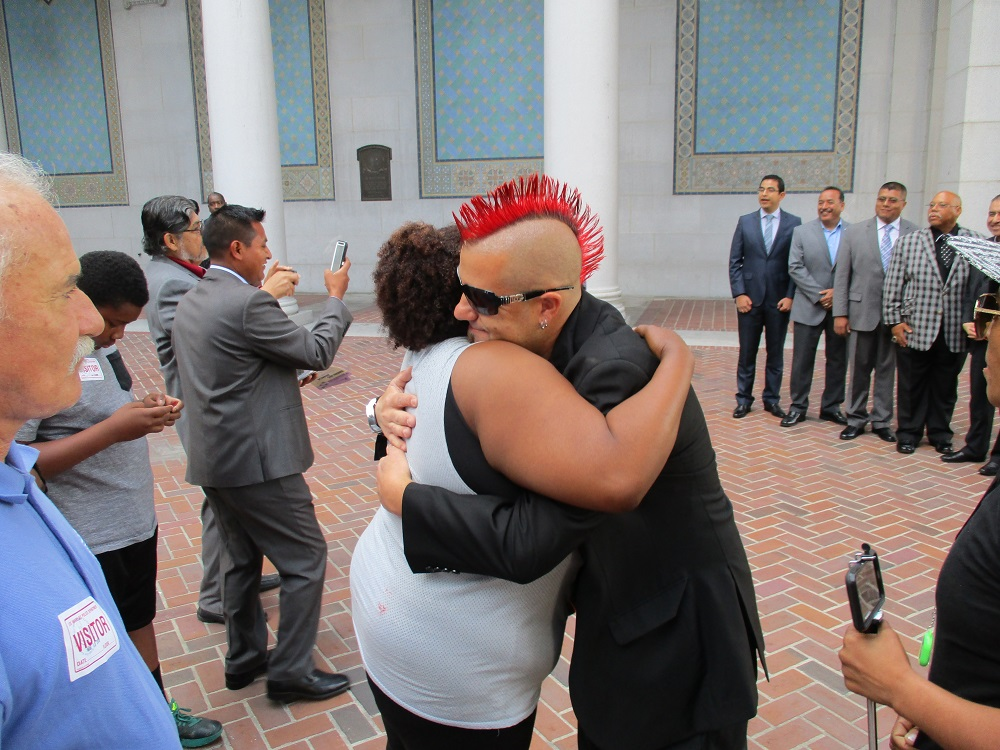 Homeless advocate Elvis Summers hugs a homeless woman at an LA protest. Photo: Bud Stratford