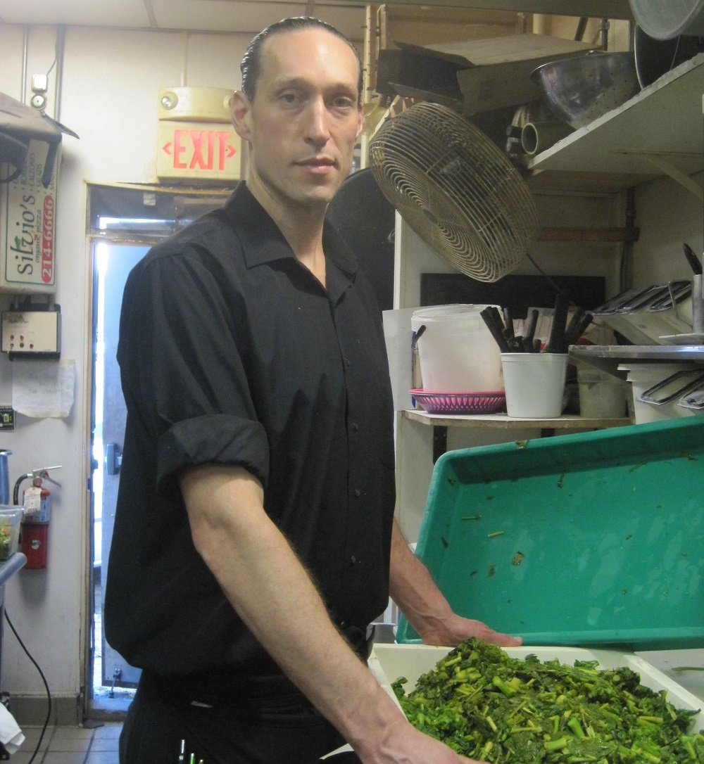 Groundcover News vendor Kevin washes rapini in Silvio's kitchen – one of his many jobs alongside selling the street paper. Photo: Susan Beckett