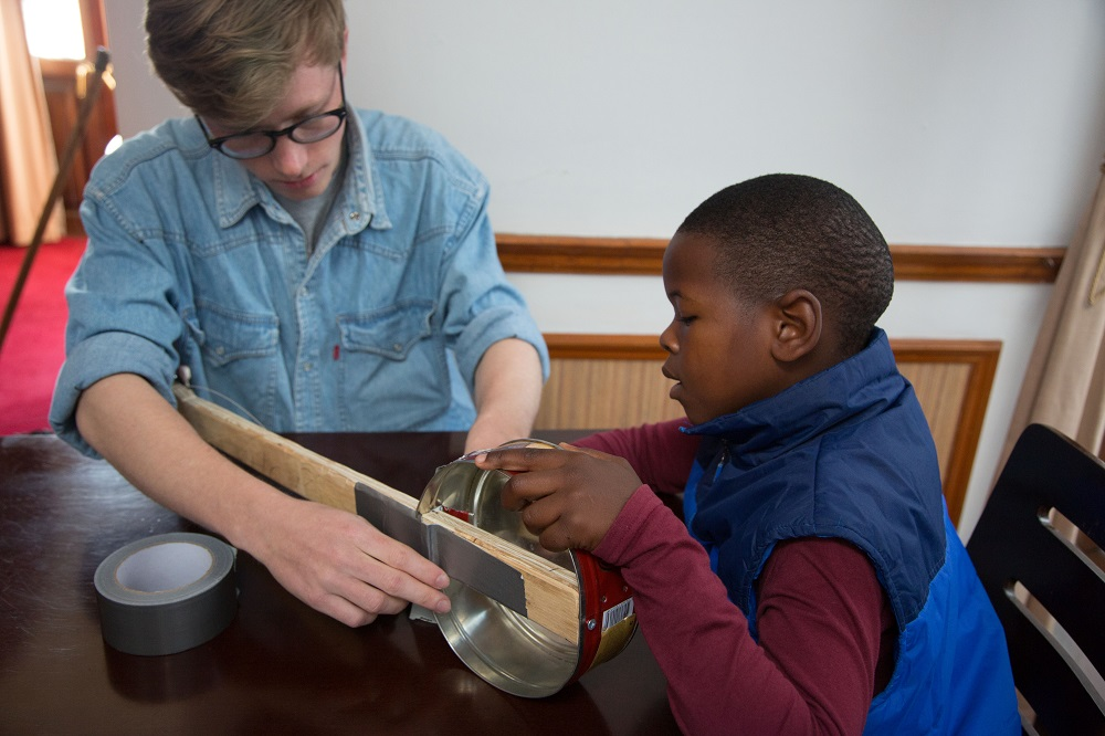 A Danish student helps the child of Big Issue South Africa vendor how to make a guitar out of recycled material during a Guitars for Good session in Cape Town. Credit: Guitars for Good