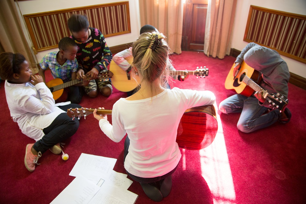 A volunteer musician with Guitars for Good teaches the children of Big Issue South Africa vendors how to play guitar during a free class held in the street paper's Cape Town office. Credit: Guitars for Good