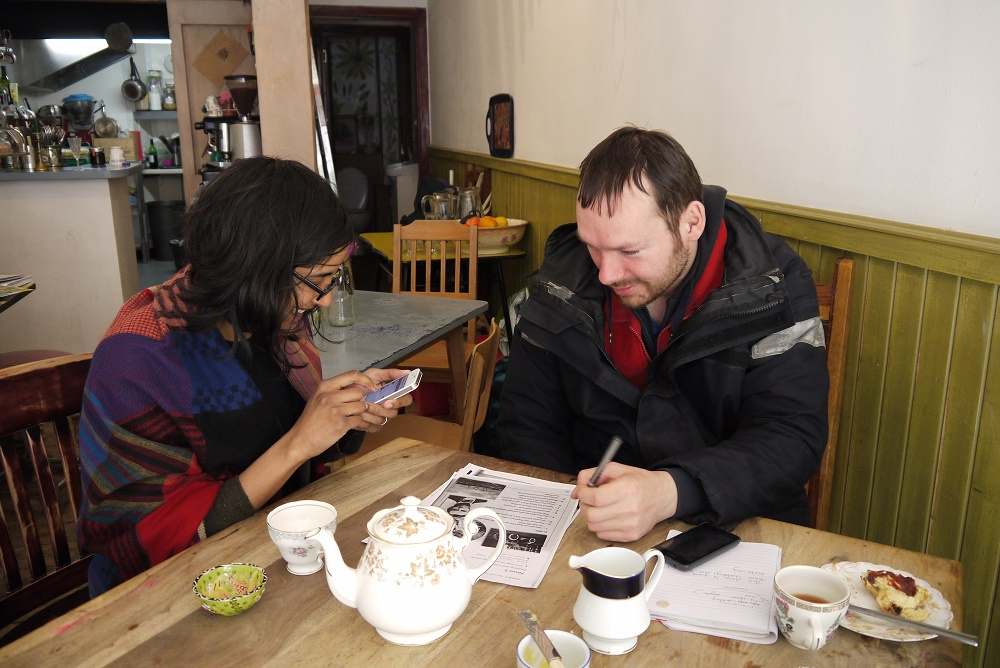 Dinushriya teaches Sebastian English using image cards, and translates on her phone. He describes what he sees in the past and present tense. The café creates a friendly and warm environment to learn, they eat fresh scones with homemade lemon curd and jam.
