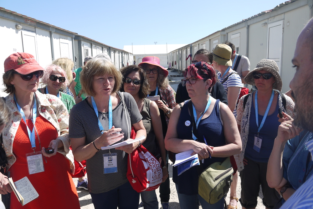 Delegates at Eleonas Refugee Camp ask Vice Mayor of Athens for Migrants and Refugees questions about the conditions of the camp. Photo by Alison Gilchrist