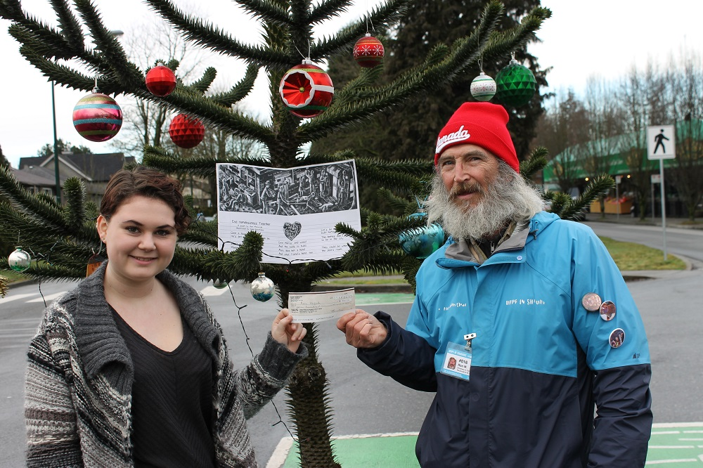 Vendor Ron McGrath poses for a photo with Elizabeth Rowlens. The Grade 11 student raised money for Ron to help his quest to help solve the homeless crisis. Credit: Megaphone