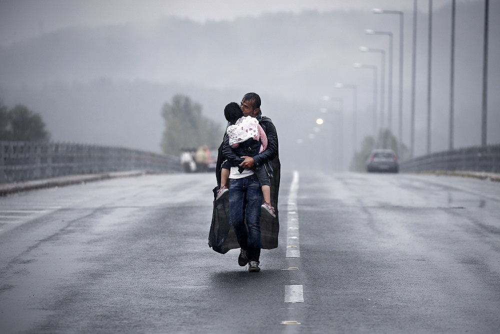 A Syrian refugee kisses his daughter as he walks through a rainstorm towards Greece's border with FYRO-Macedonia, near the Greek village of Idomeni, September 10, 2015. PHOTO: Reuters/Yannis Behrakis