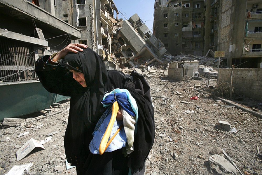 A Lebanese woman carries her belongings from her destroyed apartment in south Beirut July 23, 2006. PHOTO: Reuters/Yannis Behrakis