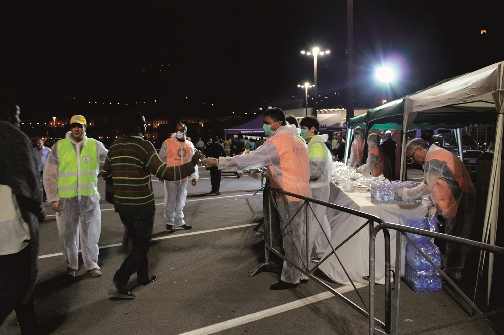 Volunteers from the association L'Abbraccio distribute meals during the arrival of migrants in Salerno. Photo courtesy of Scarp de' Tenis