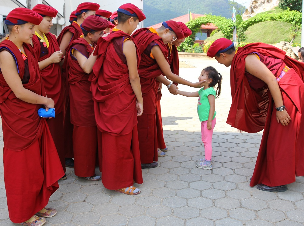 The Drukpa nuns greet a small girl in one of the nearby towns