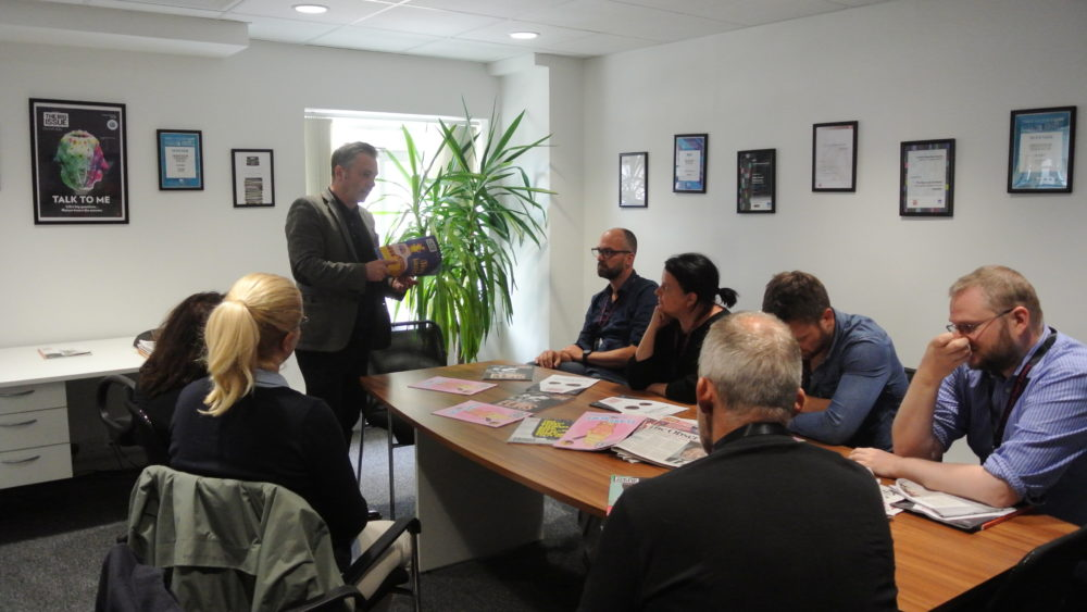 Big Issue editor Paul McNamee talks to one of the summit arrivals day groups on a visit to the Big Issue office