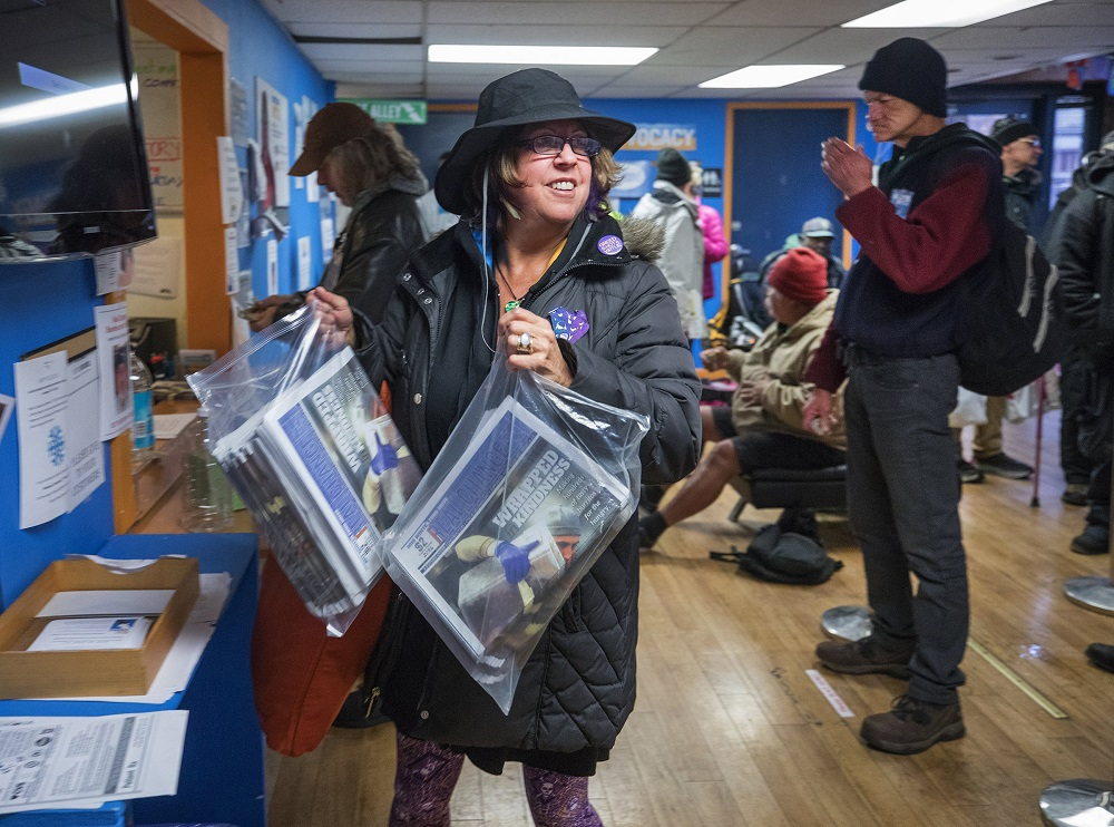 Vendor Susan Russell is a Real Change sales superstar. Here, she's picking up her weekly supply of newspapers. (Credit: Steve Ringman / The Seattle Times)