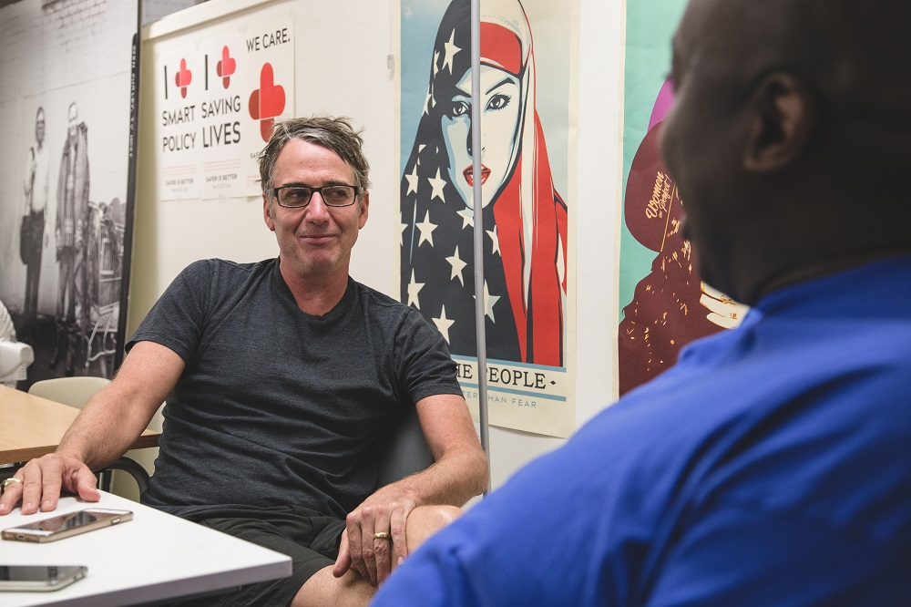 Vendor Darrell Wren chats to Stone Gossard at the Real Change office. (Credit: Matthew S. Browning)