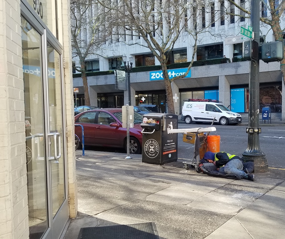A man sleeps on the sidewalk in front of the 7-Eleven by the Multnomah County Courthouse in January, despite the loud ringing noise radiating from the building. [Credit: Street Roots]